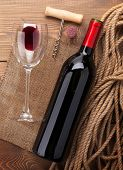 Red wine bottle, glass, cork and corkscrew. View from above over rustic wooden table background