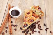 baked food: apple pie on wooden table served with coffee cup and cinnamon sticks