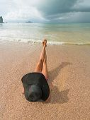 watching the coming sea storm - beautiful woman lying on the beach