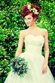 Beautiful smiling bride with chaming red hair. Wedding dress and accessories. Wedding decoration.
