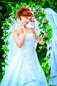 foto of wedding arch  - Beautiful bride with chaming red hair stands under the wedding arch - JPG