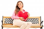 Beautiful girl holding a red heart seated on a wooden bench isolated against white background