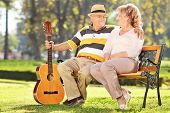 Mature man sitting with his wife in park and holding a guitar