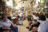 DUBROVNIK, CROATIA - MAY 28, 2014: Hrvoje CIKATO, owner of traditional barber shop Cikato with his customers.  Locals often come for chat and to have drink or two with owner.