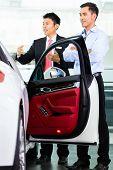 Asian Car Salesman selling auto to customer