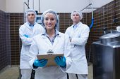 stock photo of clipboard  - Girl holding a clipboard with these colleagues behind her in the factory - JPG
