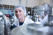 Close up of a man wearing a hair net looking at the camera in the factory