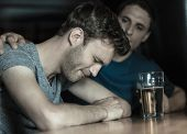 picture of upset  - Caring friend comforting upset man in a bar - JPG