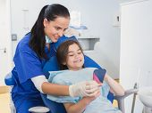 Pediatric dentist and young patient holding a mirror in dental clinic