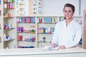 image of coat  - Smiling trainee in lab coat writing a prescription in the pharmacy - JPG