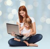 childhood, parenting and technology concept - happy mother with adorable little girl and laptop computer over holidays lights background