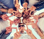 summer holidays and teenage concept - group of teenagers showing peace or victory gesture