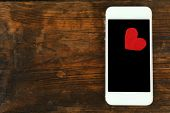 Smart mobile phone with red heart on wooden table background