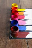 Colorful paint strokes with paint cans on white sheet of paper on wooden table background