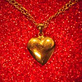 gold heart pendant on red shiny background