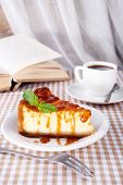 Cheese cake and cup of coffee on tablecloth on curtain background