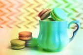 Assortment of gentle colorful macaroons in mug on color and textured background