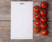 Menu sheet of paper with cherry tomatoes on rustic wooden surface background