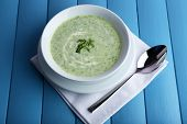 Cucumber soup in bowl on color wooden planks background