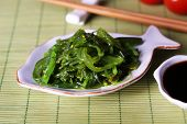 Seaweed salad in plate on bamboo mat background