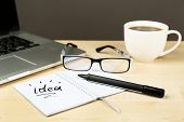 Cup of coffee with note Idea in notebook and glasses on wooden table and dark background