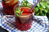 Pomegranate drink in glasses with mint and slices of lime on napkin on color wooden background