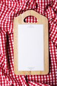Cutting board with menu sheet of paper on squared fabric background
