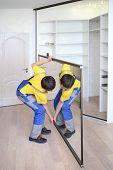 Young worker raises mirrored door on corner closet in room
