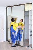 Young worker fixing mirrored door on corner closet in room
