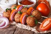 picture of meatballs  - Grilled meatballs on skewers with onions and tomatoes on an old table - JPG