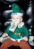 Little Baby Boy With Dollar In Mouth