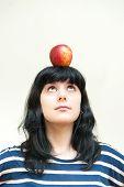 Pretty Brunette Girl Looking Red Apple On Head