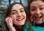 Girls With A Mobile Phones Having Fun Outside.