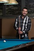 Portrait Of A Young Male Model Playing Billiards