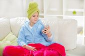 Teenager with towel on her head and mirror on her hands