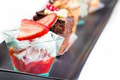 pic of fancy cakes  - delicious strawberry cake with cream in front of little chocolate and coffee cakes on black dish - JPG