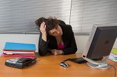 picture of upset  - Woman upset at her desk in the office - JPG