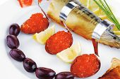 fish olives and red caviar on white plate