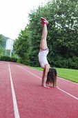 young girl make handstand at sport field