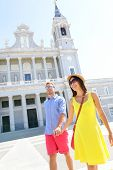 Couple walking holding hands in Madrid, Spain in front of landmark and tourist attraction Almudena Cathedral.