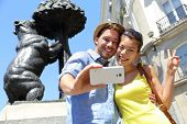 Tourists taking selfie photo pictures by famous bear statue Madrid on Puerta del Sol. Young couple using smartphone camera at tourist attraction Bear and the Madrono Tree, symbol of Madrid, Spain.