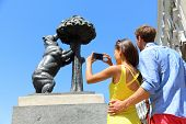 Tourists taking pictures of famous bear statue in Madrid on Puerta del Sol. Young couple at tourist attraction landmark Bear and the Madrono Tree, symbol of Madrid, Spain.