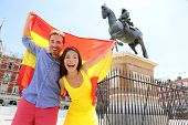 stock photo of cheers  - Madrid people showing Spain flag on Plaza Mayor cheerful and happy in Spain - JPG