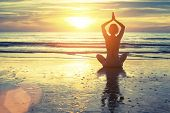 image of breathing exercise  - Silhouette of yoga woman meditating on the ocean beach - JPG