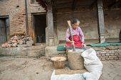 BHAKTAOUR, NEPAL - DEC 7, 2013: Unidentified Nepalese woman working in the his pottery workshop. More 100 cultural groups have created an image Bhaktapur as Capital of Nepal Arts.