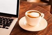 picture of latte  - Hot latte coffee cup in a white cup on a table laptob in coffee shop - JPG