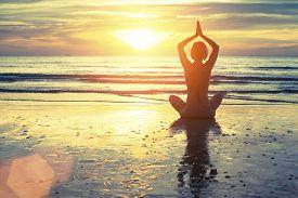 foto of sea life  - Silhouette of yoga woman meditating on the ocean beach - JPG