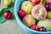 stock photo of peach  - Juicy peaches and apricots in wooden bowl - JPG