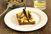 picture of scrambled eggs  - Sandwich with scrambled eggs and sprats on rye bread - JPG