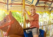 foto of carnival ride  - Cute little smiling boy riding on a Carnival Carousel at an amusement park or theme park - JPG